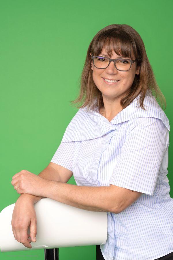 Stéphanie Liiri s'attenant à une chaise, lunette et cheveux châtains clair, sur un fond vert