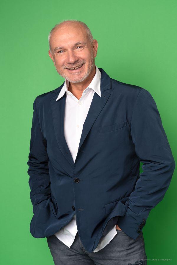 Éric Granddidier en costume, debout et devant un fond vert