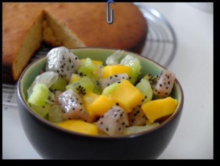 une salade de fruits exotiques colorée dans un bol avec un gâteau en arrère plan