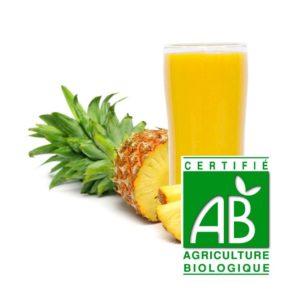 un ananas coupé en tranches avec un verre de jus d'ananas et logo agriculture biologique
