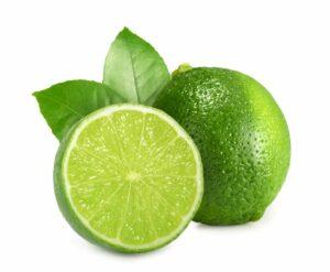 un citron vert surgelé et un demi citron vert surgelé et deux feuilles sur fond blanc